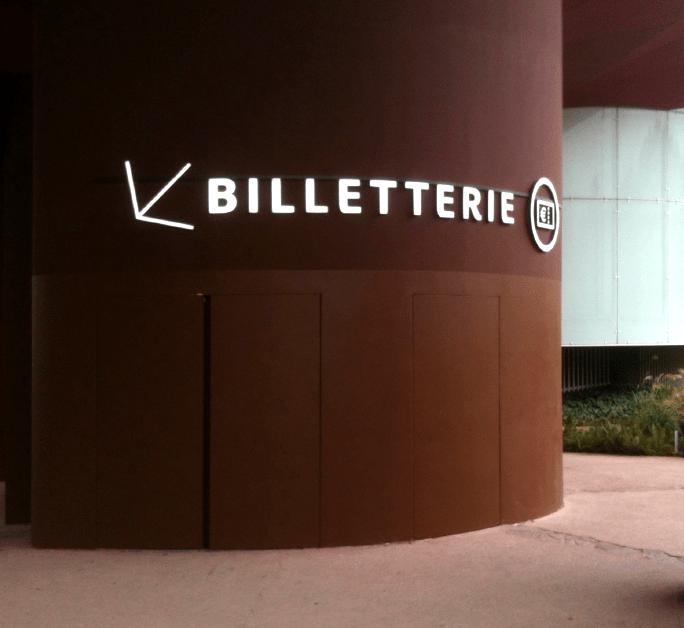 Lettres lumineuses orientant vers la billetterie dans le jardin du musée