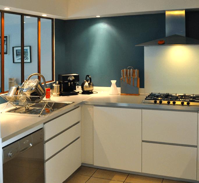 Vue de la cuisine après travaux - Création d'une baie en vitrage atelier pour créer un apport de lumière naturelle.